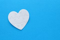 Top view image of paper heart puzzle over pastel background. Top view image of paper white heart puzzle over blue background. Health care, donate, world heart stock photography