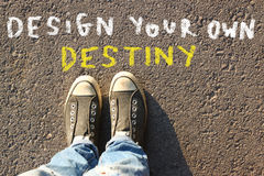 Top view image of person in jeans and sneakers with the text - design your own destiny Royalty Free Stock Image