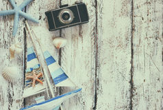 Top view image of photo camera, wood boat, sea shells and star fish over wooden table.  Royalty Free Stock Images