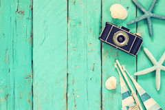 Top view image of photo camera, wood boat, sea shells and star fish over wooden table.  Stock Image