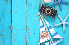 Top view image of photo camera, wood boat, sea shells and star fish over wooden table Stock Image