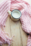 Top view image of a pink cosy knitted scarf with a Cup of coffee on wooden table Royalty Free Stock Photo