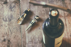 Top view image of red wine bottle and corkscrew. Over wooden table. retro style image selective focus Royalty Free Stock Images