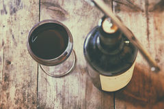 Top view image of red wine bottle and corkscrew. Over wooden table. retro style image selective focus Stock Photography