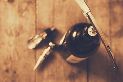 Top view image of red wine bottle and corkscrew. Over wooden table. retro style image selective focus Royalty Free Stock Photos