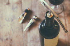Top view image of red wine bottle and corkscrew. Over wooden table. retro style image selective focus Royalty Free Stock Image