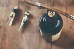 Top view image of red wine bottle and corkscrew. Over wooden table. retro style image selective focus Royalty Free Stock Photography