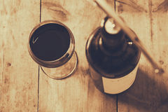 Top view image of red wine bottle and corkscrew. Over wooden table. sepia style image selective focus Stock Photo