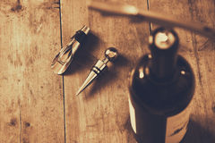Top view image of red wine bottle and corkscrew. Over wooden table. sepia style image selective focus Royalty Free Stock Images