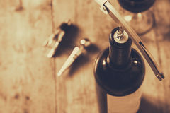 Top view image of red wine bottle and corkscrew. Over wooden table. sepia style image selective focus Stock Photos