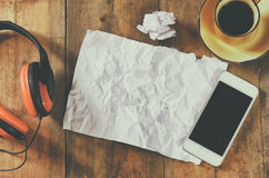 Top view image of smartphone with blank screen headphones folded paper and coffee cup. room for text. faded style image Stock Photos