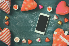 Top view image of smartphone, colorful heart shape chocolates, fabric hearts on blackboard background. valentine's day celebration Stock Images