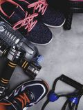 Top view image of sport shoes, dumbbells, press roll, water, expander. Fitness or workout equipment. Weight loss and sports. Concept with copy space stock photography
