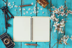 Top view image of spring white cherry blossoms tree, open blank notebook, old camera on blue wooden table Stock Photography