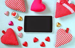 Top view image of tablet, colorful heart shape chocolates, fabric hearts on wooden background. valentine's day celebration concept Stock Photos