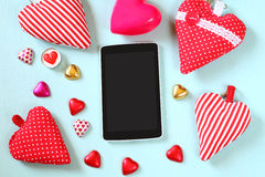 Top view image of tablet, colorful heart shape chocolates, fabric hearts on wooden background. valentine's day celebration concept Stock Images