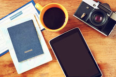 Top view image of tablet with empty screen, old camera passport and flight boarding pass.  Royalty Free Stock Image
