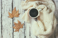 Top view image of white cozy knitted sweater with to cup of coffee and autumn leaves on a wooden table Stock Images