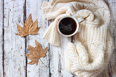 Top view image of white cozy knitted sweater with to cup of coffee and autumn leaves on a wooden table Royalty Free Stock Photography