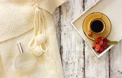 Top view image of white cozy knitted sweater with to cup of coffee and perfume bottle on a wooden table Royalty Free Stock Photography