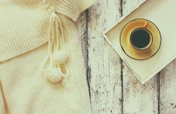 Top view image of white cozy knitted sweater with to cup of coffee on a wooden table. faded retro filtered photo Stock Photos