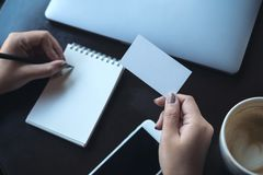A woman`s hands holding empty white business card and writing on blank notebook with laptop and mobile phone on the table. Top view image of a woman`s hands Royalty Free Stock Photography