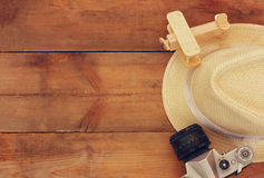 Top view image of wood aeroplane, fedora hat and old camera over wooden table Stock Photo