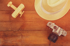 Top view image of wood aeroplane, fedora hat and old camera over wooden table Royalty Free Stock Images