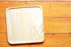Top view image of wooden blank tray placed on table with copy space, textured wooden background. Top view image of wooden blank tray placed on wooden table with royalty free stock photography