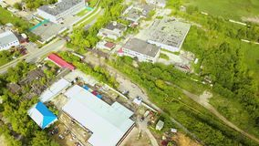 Top view of industrial area with factory buildings. Action. Rural industrial area with production buildings and green stock video footage