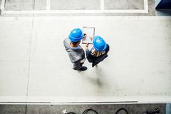 A top view of an industrial man and woman engineer with clipboard in a factory. A top view of an industrial men and women engineer with clipboard in a factory royalty free stock photos
