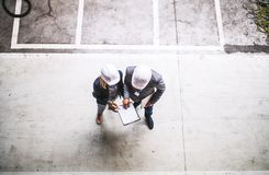 A top view of an industrial man and woman engineer with clipboard in a factory. royalty free stock photo