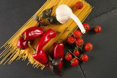 Top view of ingredients for traditional italian cuisine - dry pasta. Vegetables, fresh tomatoes, garlic, bell pepper and basil. Concept of detox and vegetarian Stock Image