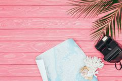 Top view of instant print camera with coral and map on pink. Wooden surface stock images