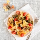 Top view of italian colored pasta farfalle with basil and tomatoes. royalty free stock photos