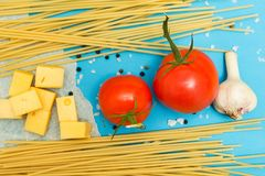 Top view of Italian ingredients of pasta and vegetables tomatoes, pasta, garlic, pepper, cheese, spices on a blue background royalty free stock photography