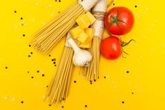 Top view of Italian ingredients of pasta and vegetables tomatoes, pasta, garlic, pepper, cheese, spices on a yellow background. royalty free stock photo
