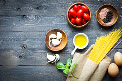Top view of italian ingredients for tomato and basilic spaghetti. With olive oil and garlic over a wood background Stock Photo