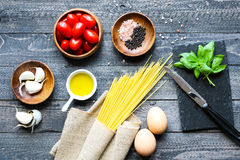 Top view of italian ingredients for tomato and basilic spaghetti. With olive oil and garlic over a wood background Royalty Free Stock Images