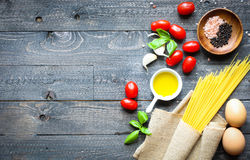 Top view of italian ingredients for tomato and basilic spaghetti. With olive oil and garlic over a wood background Royalty Free Stock Image