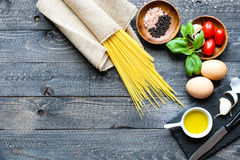 Top view of italian ingredients for tomato and basilic spaghetti. With olive oil and garlic over a wood background Stock Images