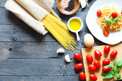 Top view of italian ingredients for tomato and basilic spaghetti. With olive oil and garlic over a wood background Stock Photos