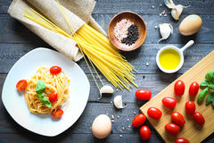 Top view of italian ingredients for tomato and basilic spaghetti. With olive oil and garlic over a wood background Royalty Free Stock Photo