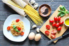 Top view of italian ingredients for tomato and basilic spaghetti. With olive oil and garlic over a wood background Stock Image