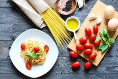 Top view of italian ingredients for tomato and basilic spaghetti. With olive oil and garlic over a wood background Stock Photography