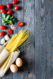 Top view of italian ingredients for tomato and basilic spaghetti. With olive oil and garlic over a wood background Royalty Free Stock Photography