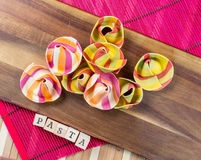Top view of Italian ravioli on a wooden board with the wooden sign pasta Royalty Free Stock Photo