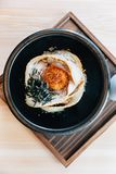 Top view of Japanese Chashu Don: Steam Rice topping with Roasted Pork Belly, Yolk, Dried Seaweed and Saffron. Served in black ceramic bowl stock photos