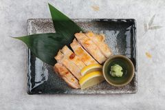 Top view of Japanese chicken grilled with sea salt served with sliced lemon and wasabi in stone rectangle plate on washi. Royalty Free Stock Photography
