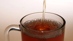Top view, jet of hot tea fills the glass cup stock footage